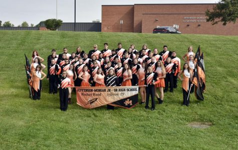 All band members from instument players to flag holders pose with one another for a picture.